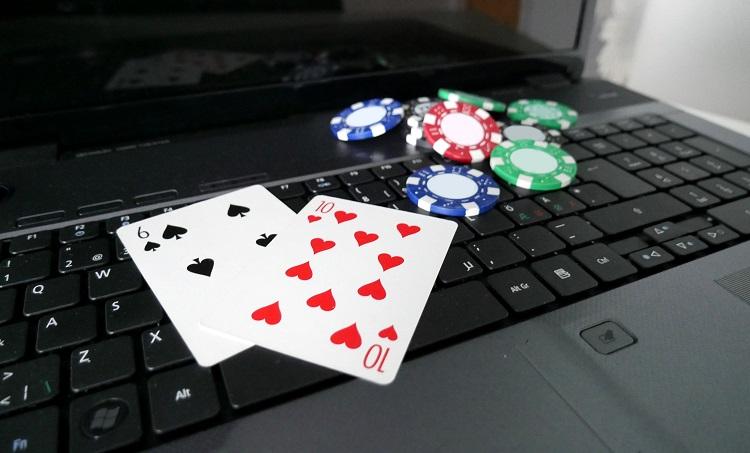 Laptop mit Pokerkarten und Chips